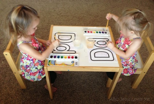 Twin girls sitting at a table painting.