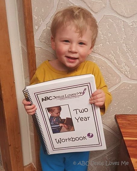 Little boy holding ABCJesusLovesMe Curriculum book.