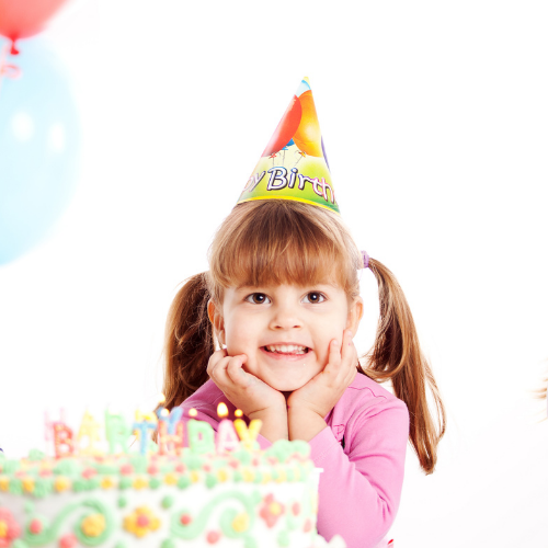Little girl wearing a birthday hat at birthday party.