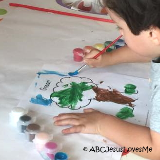 Little boy painting a Creation worksheet