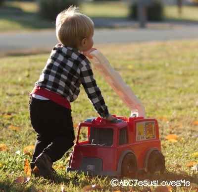 Child playing outside with firetruck.
