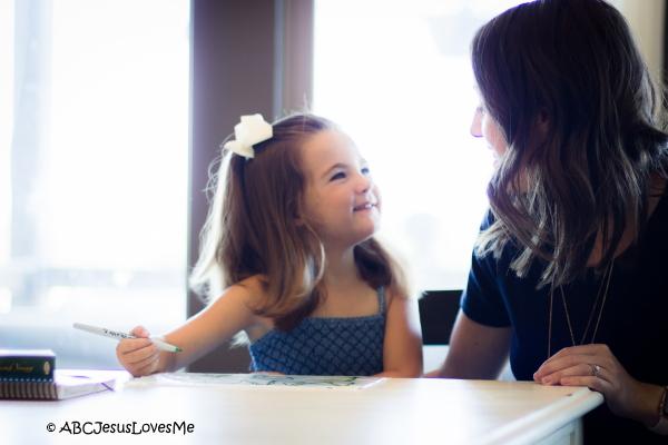 Adult teaching preschool child how to write.